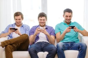 Three friends playing mobile app games