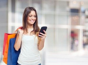 Woman on her phone holding shopping bags